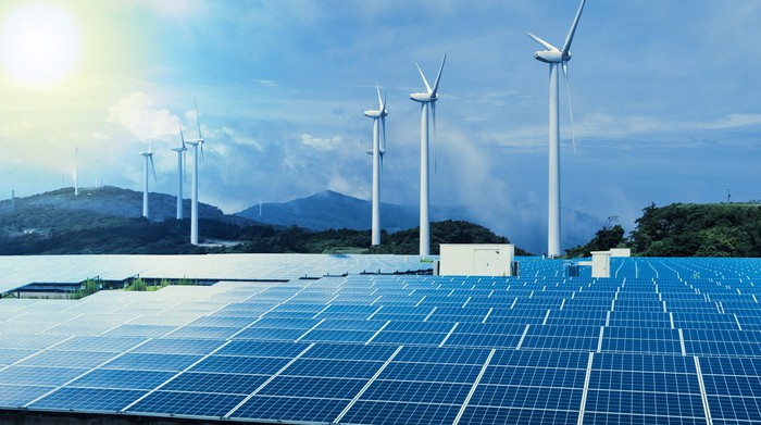 Solar and wind farm with a setting sun on the horizon.