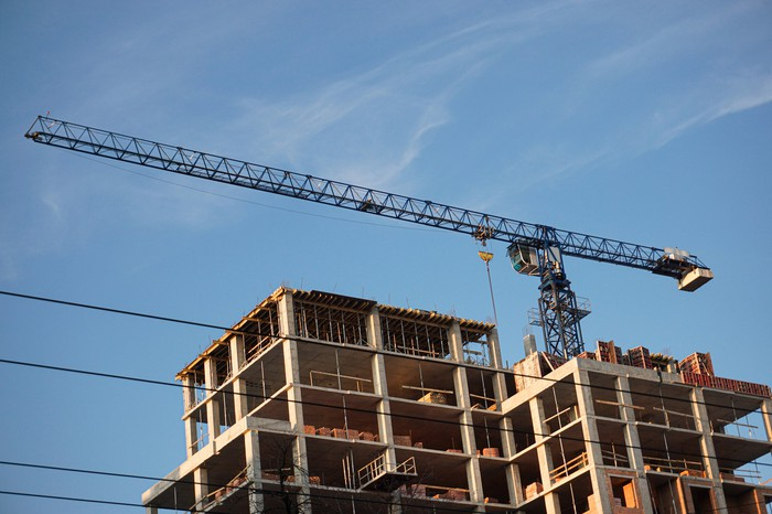 Crane on top of a large construction site.