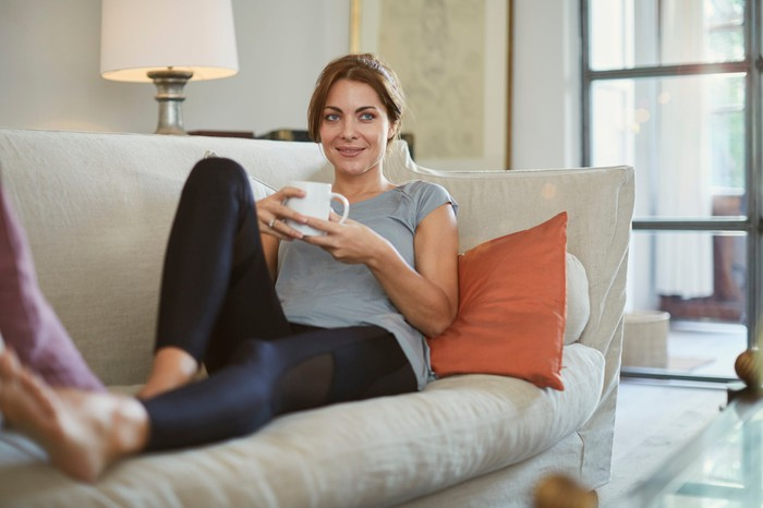 Person in yoga pants is lying on sofa and holding mug.