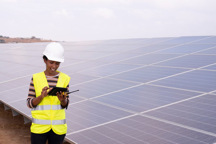 Engineer at a power station with solar panels in the background.