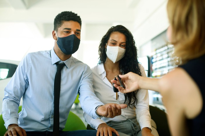 A masked couple shopping for a car during the pandemic.