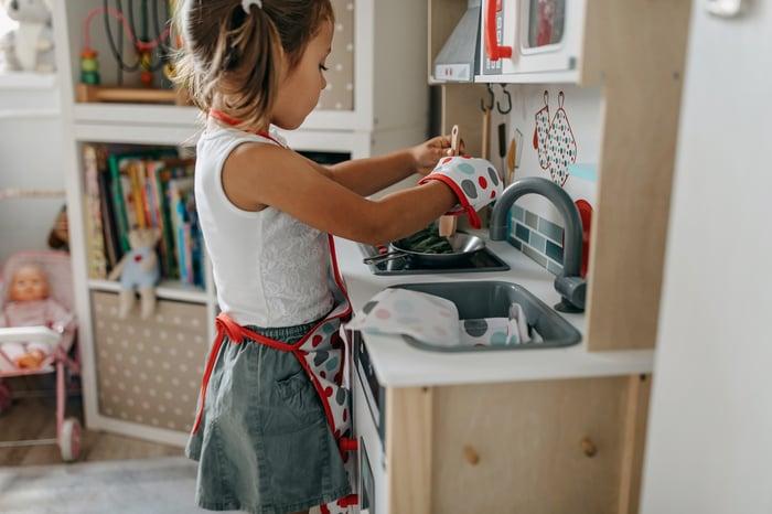 A child plays in their toy kitchen