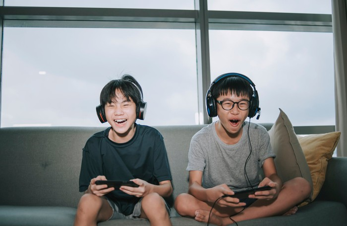 Two kids happily play video games sitting on a couch