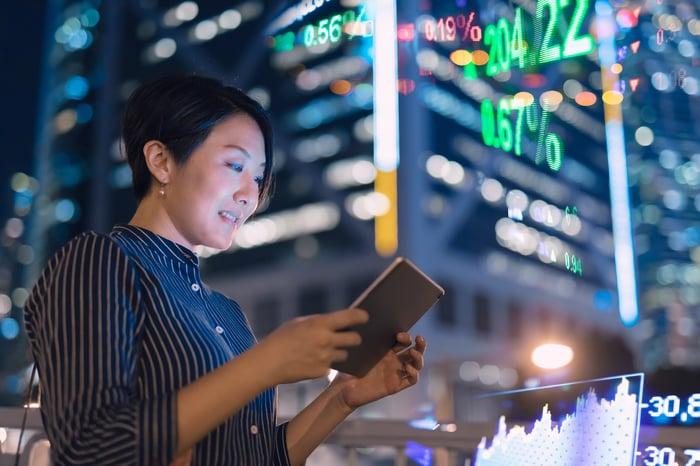 Un homme d'affaires asiatique vérifie les données sur une tablette devant le panneau d'affichage de la bourse de Hong Kong.