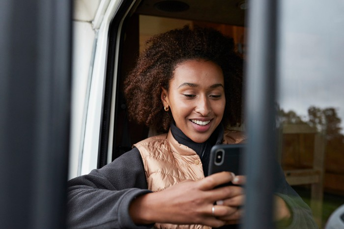 Person happily engaging with smartphone.