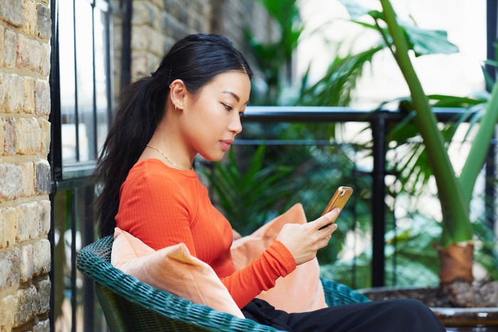 A person sits on a porch looking at their smartphone.