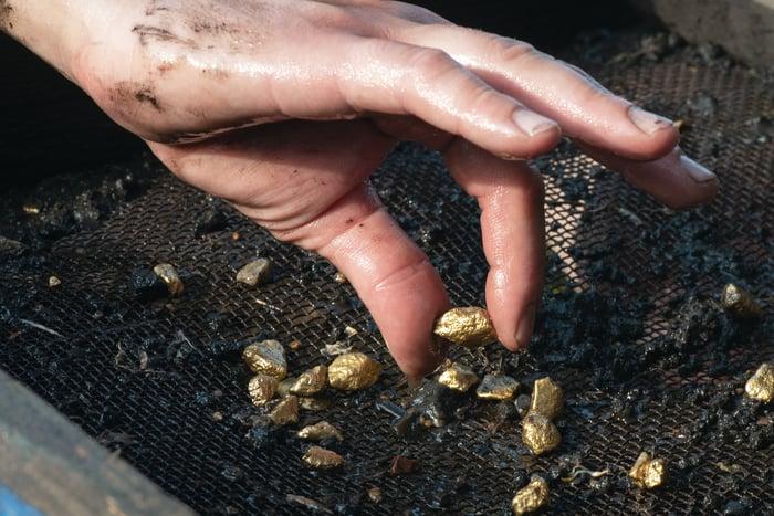 Une main ramasse des pépites d'or dans la saleté qu'elles tamisent.