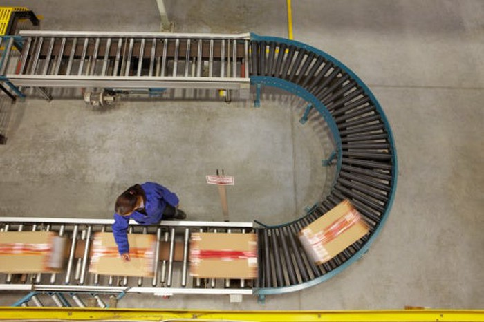 Person moving boxes on conveyor belt.