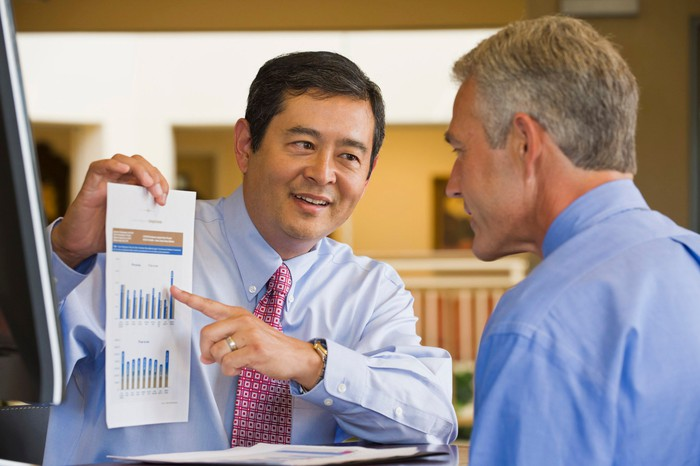Businessman showing a bar chart to another businessman.