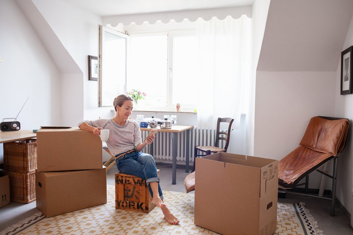 A person in an apartment sitting on a box looking at their phone.