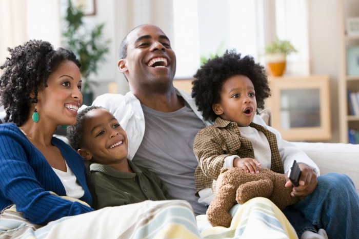 Young family watching television together.
