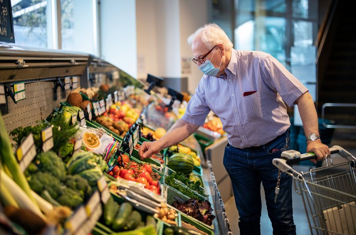 A senior person wearing a mask and picking vegetables at a grocery store.