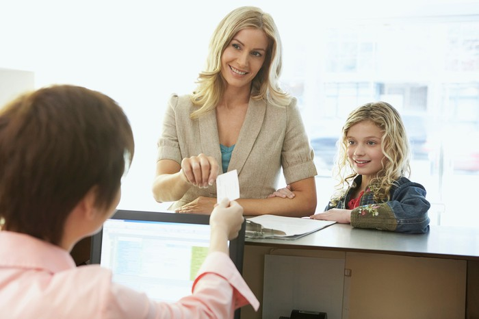 Adult and child smiling as they pay the bill in doctor's office.