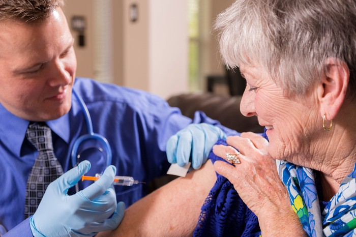 A physician administering a vaccine into the upper right arm of an elderly patient.