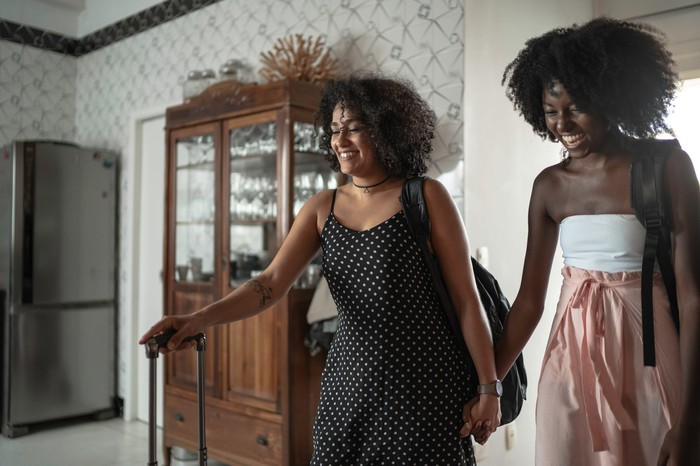 Two women holding hands and carrying luggage while arriving at their bed and breakfast.
