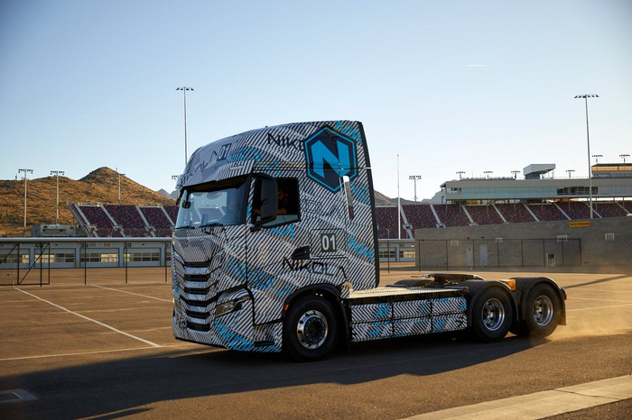 A Nikola electric vehicle semi-tractor chassis sits in a parking lot.