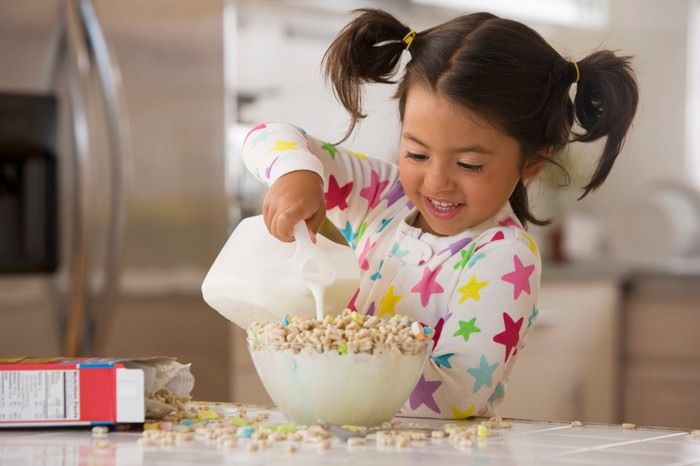 A young child pours milk into an overflowing bowl of cereal.