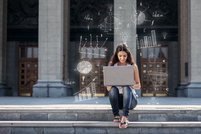 A girl on a laptop computer outside a university building.