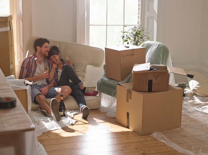 A smiling couple surrounded by boxes, sitting on a couch cushion on the floor of a home.