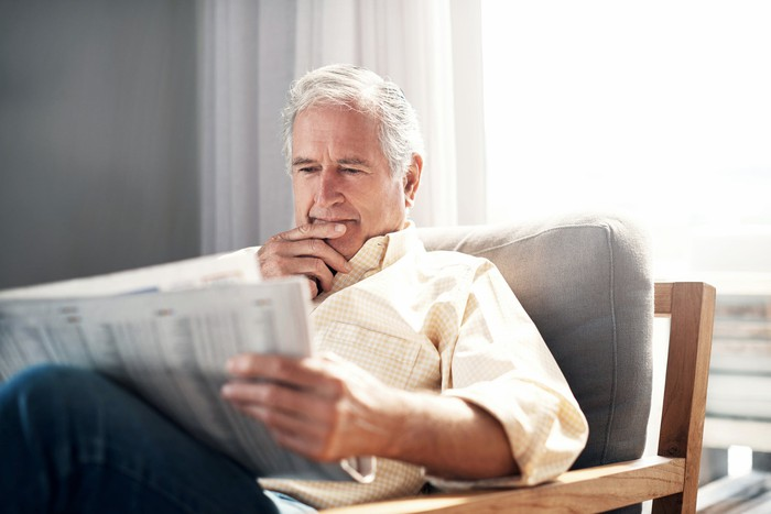 Person reading newspaper while sitting on a comfy chair.