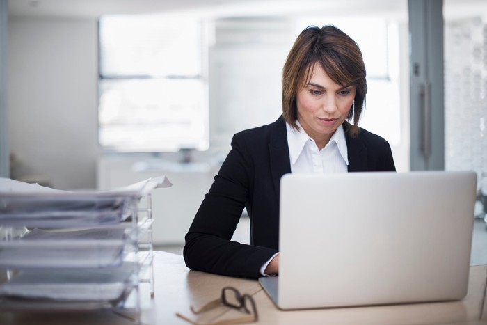 Business person typing on laptop.
