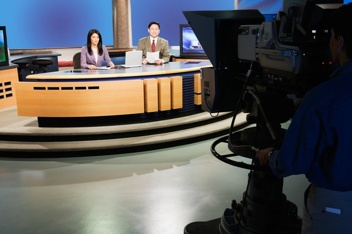 Television news broadcast desk with two announcers, and camera.