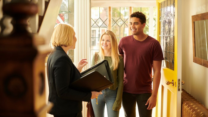 Two adults stand in the doorway of a home, speaking to a person with a binder and set of keys.