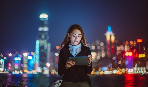 Asian woman using digital tablet at promenade against illuminated cityscape at night source Getty