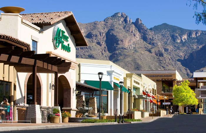 A row of stores at La Encantada in Tucson, with mountains in the background.