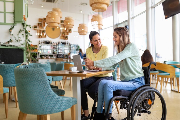Two people, one in a wheelchair, using a laptop in a cafe.