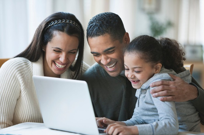 Two adults and a child smile as they look at something on a laptop in home setting.
