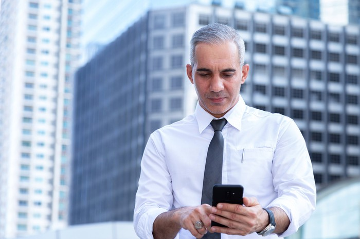 Person in professional attire standing outside building looking at phone