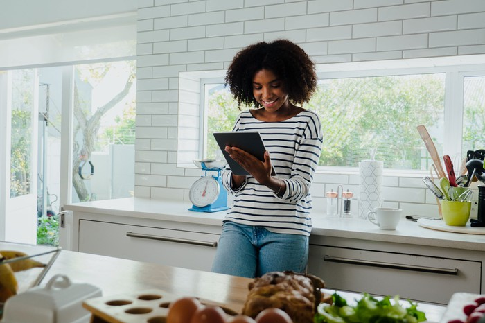 A smiling person looking at a touchscreen tablet while standing in a kitchen.