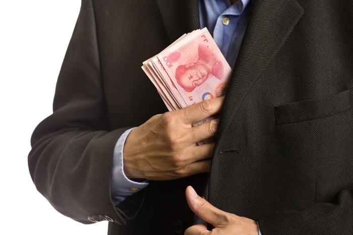 Closeup on businessman putting wad of yuan cash into suit pocket.
