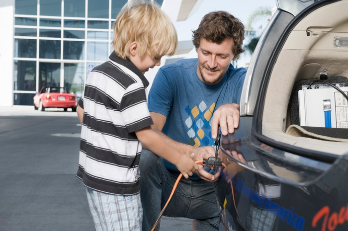 Father and son attaching electrical plug to an electric car.