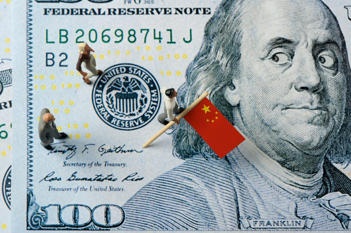 On a $100 bill Benjamin Franklin looks worriedly over his shoulder at people carrying a Chinese flag