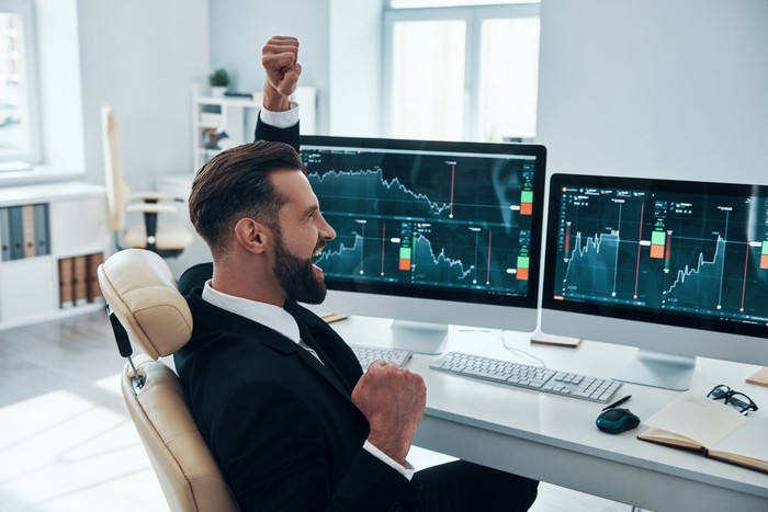 A person celebrates while looking at financial charts on two computers.
