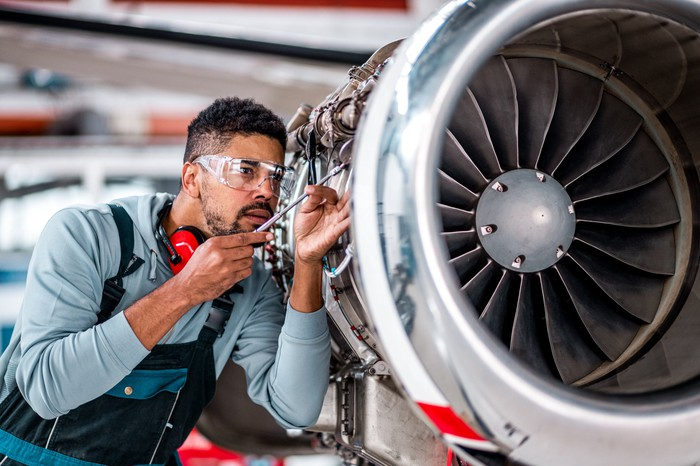 Person working on an aircraft engine.