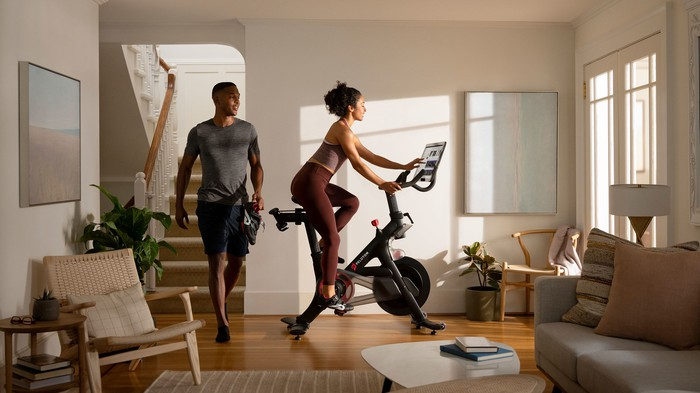 A person riding a Peloton stationary bike in a house while another person walks into the room behind them.