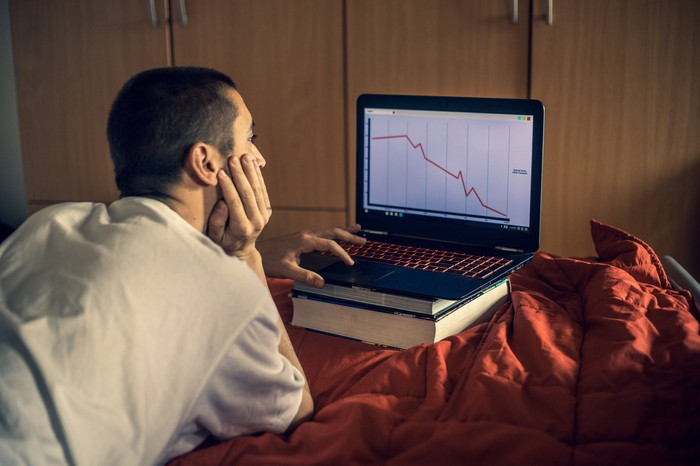 Depressed investor looking at a downward sloping stock chart.