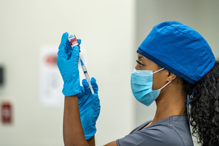 A healthcare professional holding a syringe and needle to a vaccine vial.