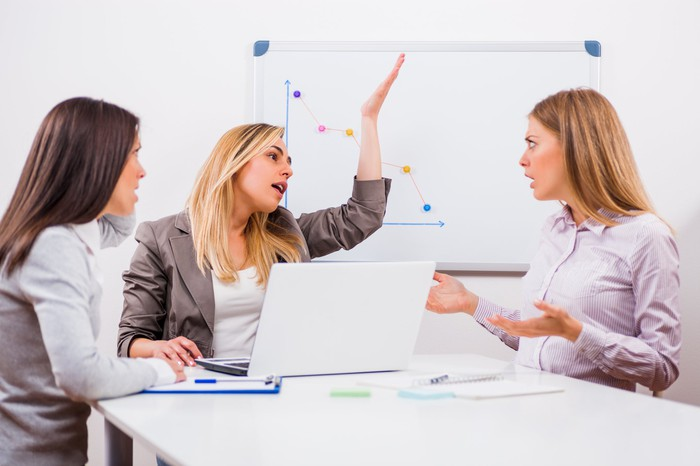 Three business professionals arguing in a conference room with a stock chart in the background.