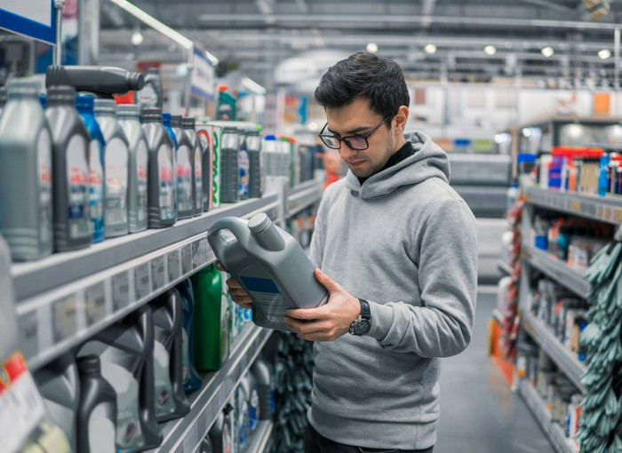 A customer in an auto parts store looks at a product container while standing in an aisle full of products