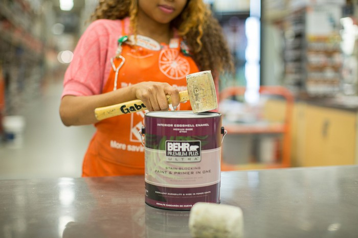 A Home Depot employee uses a rubber mallet to seal the lid on a paint can sitting on a table in a Home Depot store.