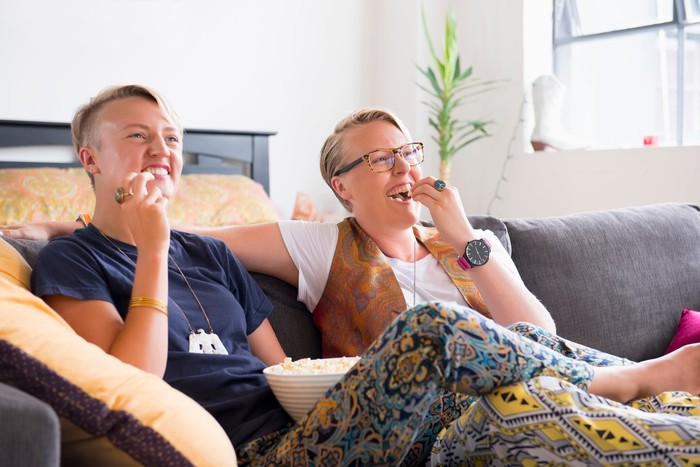 Two smiling people watch TV and eat popcorn.