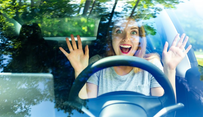 A person behind the wheel of a car smiling with their hands in the air.