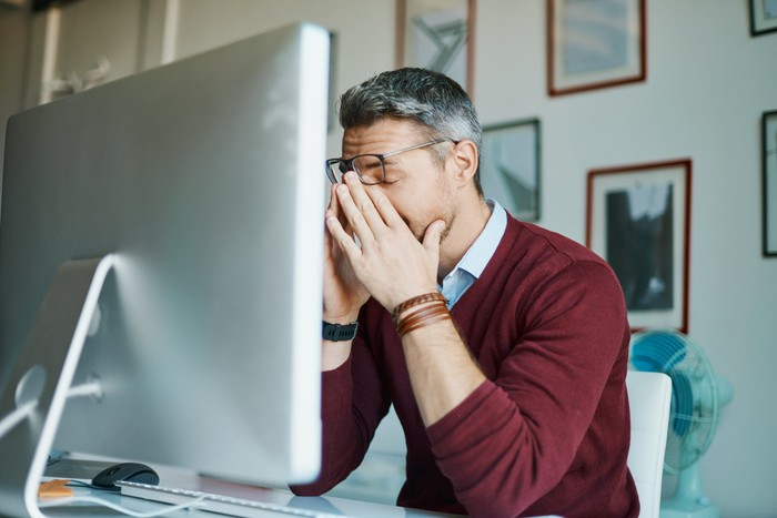 Person at computer with face in hands.