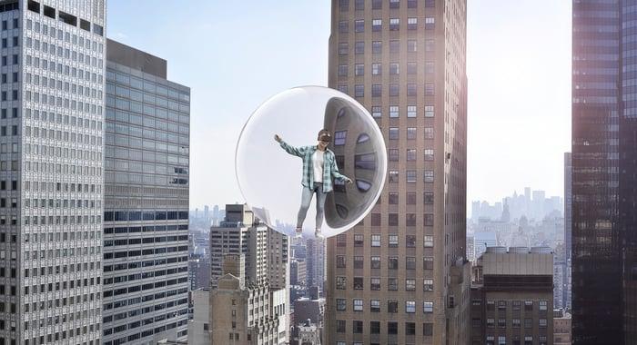 Personne portant un casque VR dans une bulle entourée de gratte-ciel.
