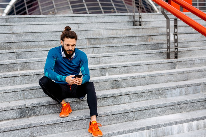 Person sitting on the steps, looking at the phone, wearing sportswear.