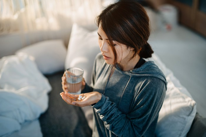 Woman takes two pills with a glass of water